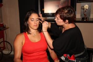Woman in red sitting in a chair, while make up is applied to her eye lids.