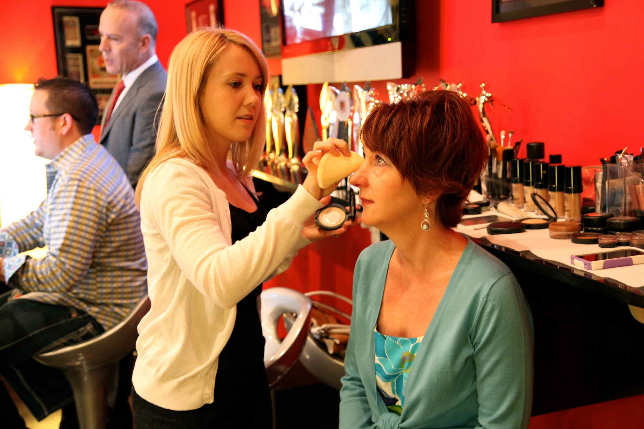 Michele Mann applying make-up to a woman.