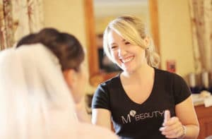 Michele Mann applying make-up to a bride.